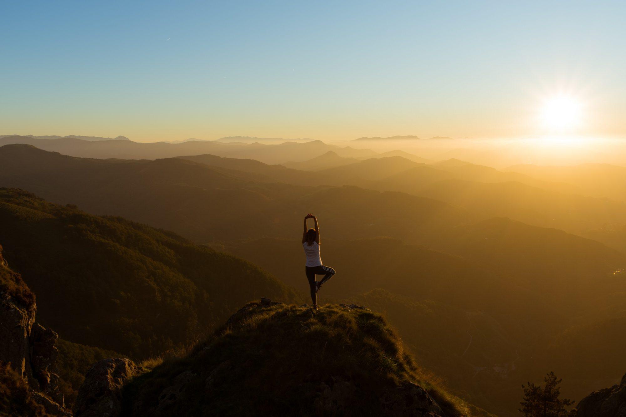 Une femme fait un figure de yoga sur un rocher tout en contemplant le coucher de soleil