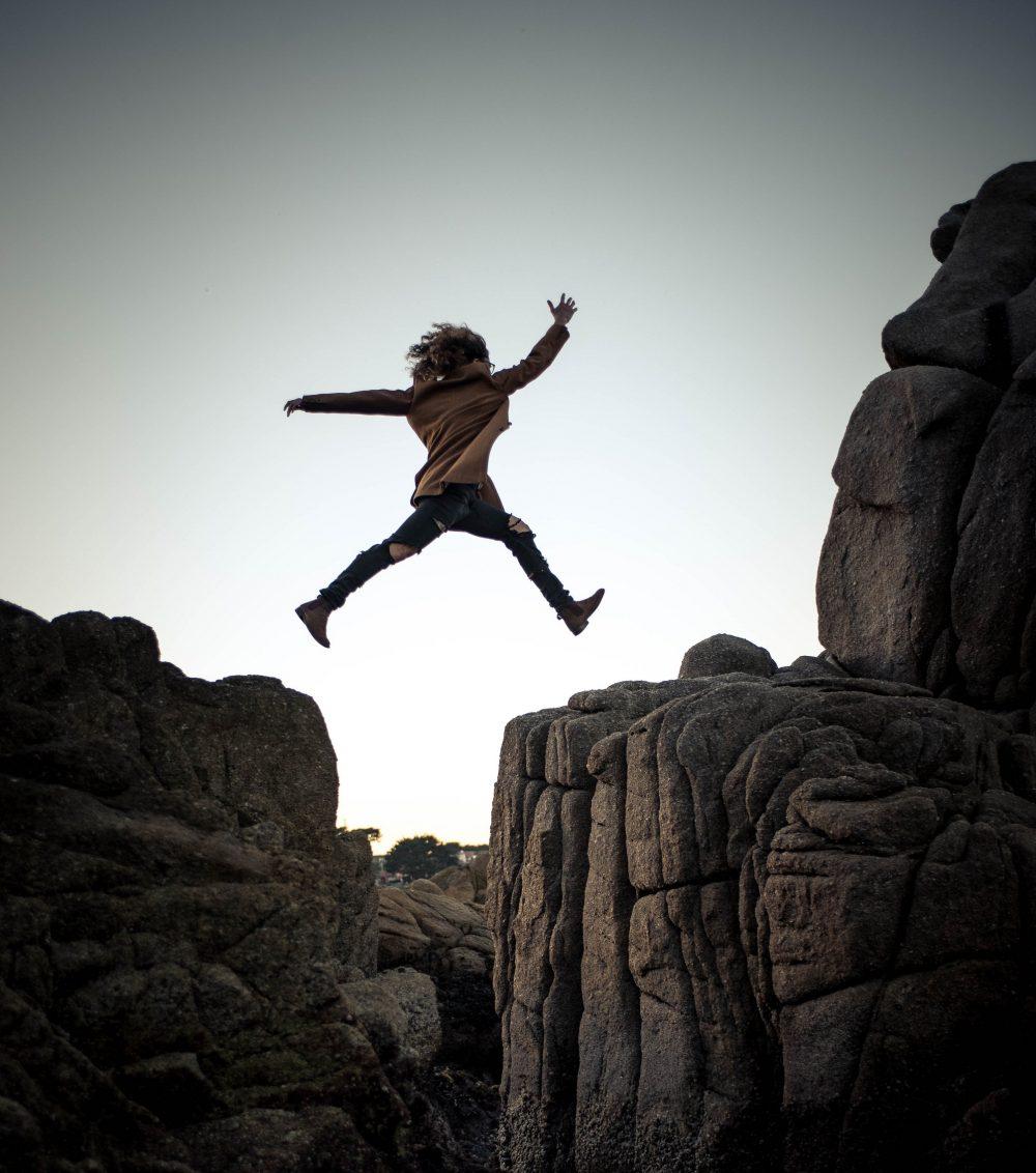 Une femme saute d'un rocher à un autre
