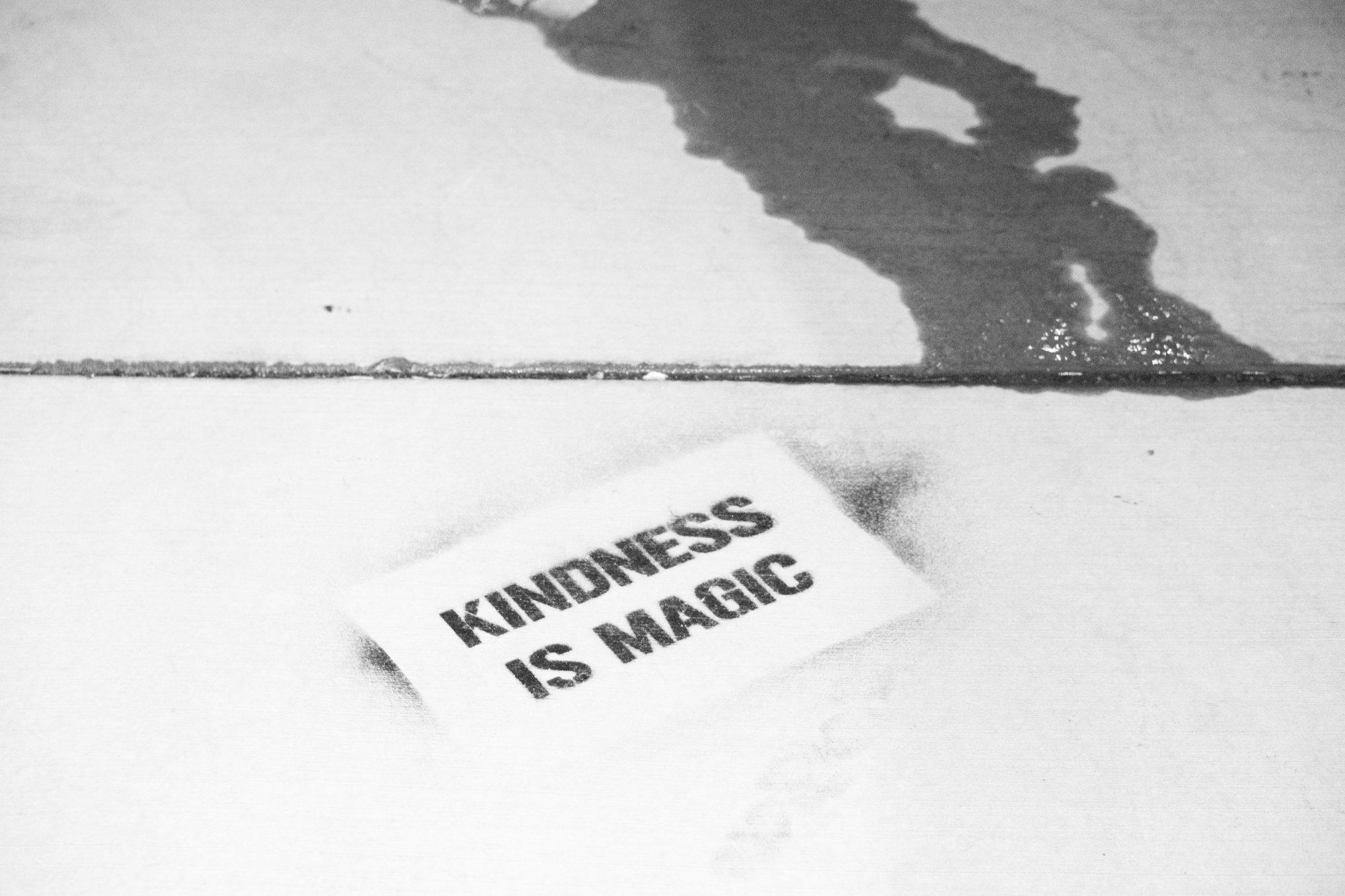 Un papier sur un sol avec dessus le texte Kindness is magic