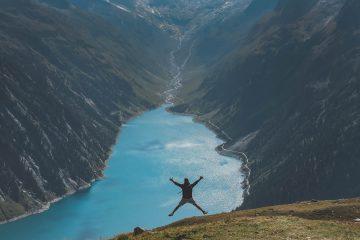 Une personne qui saute sur une montage avec un fleuve devant