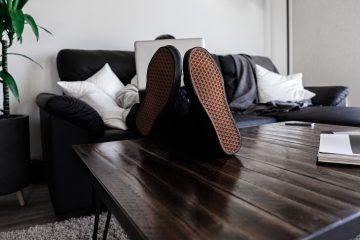 Un homme sur son ordi, assis sur son fauteuil confortablement avec les pieds sur la table basse