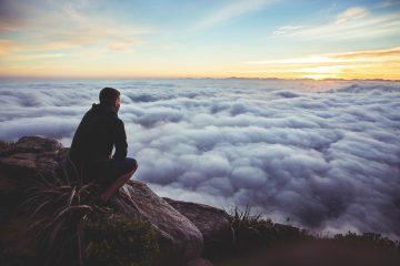 Un homme regarde l'horizon au dessus des nuages
