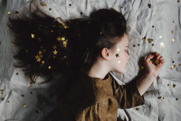 Une fille qui dort et dessus des étoiles en paillettes dorées